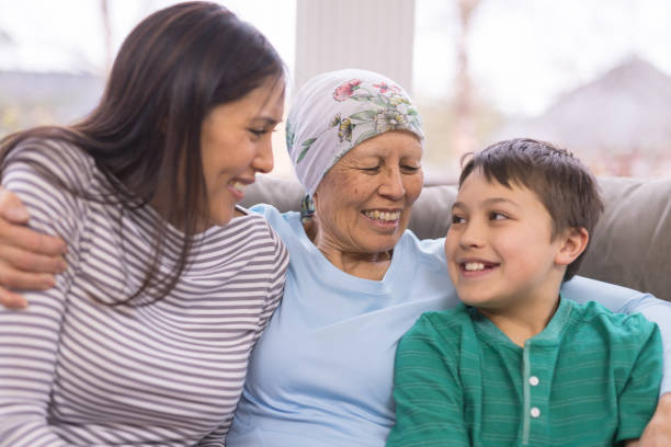 Happy ethnic woman with cancer embraces her adult daughter and grandson An ethnic woman with cancer and wearing a headcovering is embracing her mid-3os daughter and 10 year old grandson. They are sitting on a couch and are smiling. old mother son asian stock pictures, royalty-free photos & images