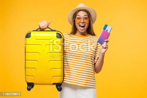 Happy European girl with suitcase and airplane tickets isolated on yellow background excited about trip