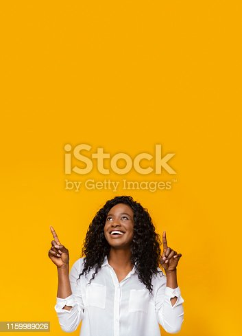 Great offer! Excited african american woman pointing upward at empty space, yellow background