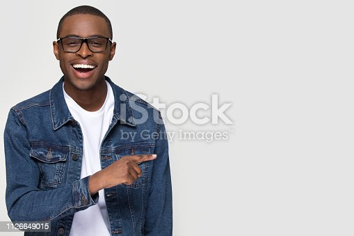 istock Happy excited african man laughing pointing finger at copy space 1126649015