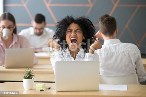 istock Happy excited african-american employee celebrating online win or business success 963814432