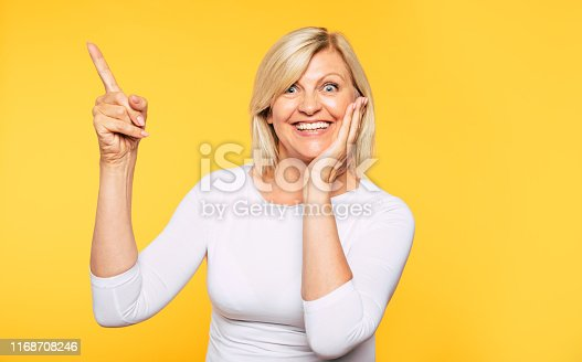 istock Happy excited beautiful blonde senior woman in casual clothes is pointing away on yellow background. 1168708246