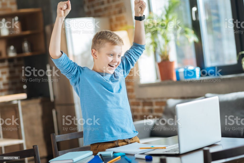 Positive mood. Joyful delighted nice boy looking at the laptop screen...