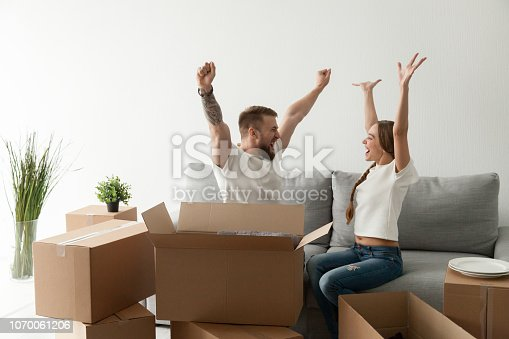 istock Happy excited couple sitting together on couch celebrating moving 1070061206