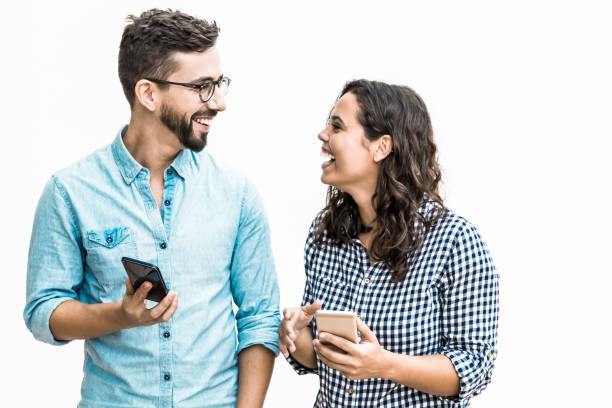 Happy excited couple with smartphones discussing awesome news stock photo