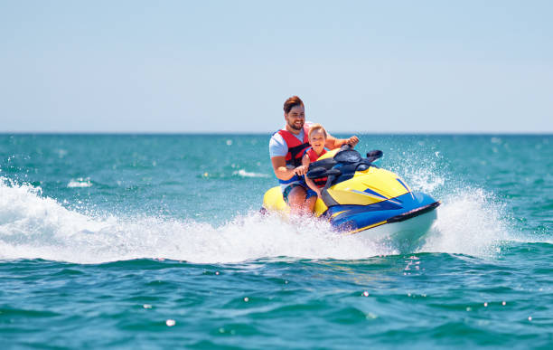 happy, excited family, father and son having fun on jet ski at summer vacation stock photo