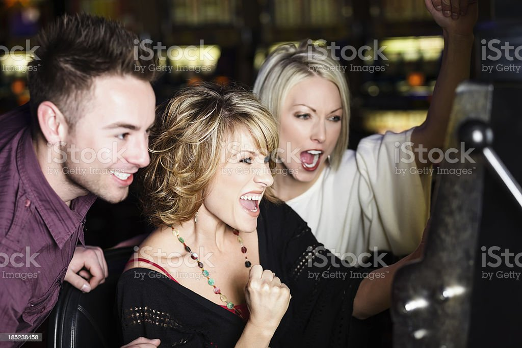 Happy Excited Group Winning at Slot Machine In a Casino stock photo