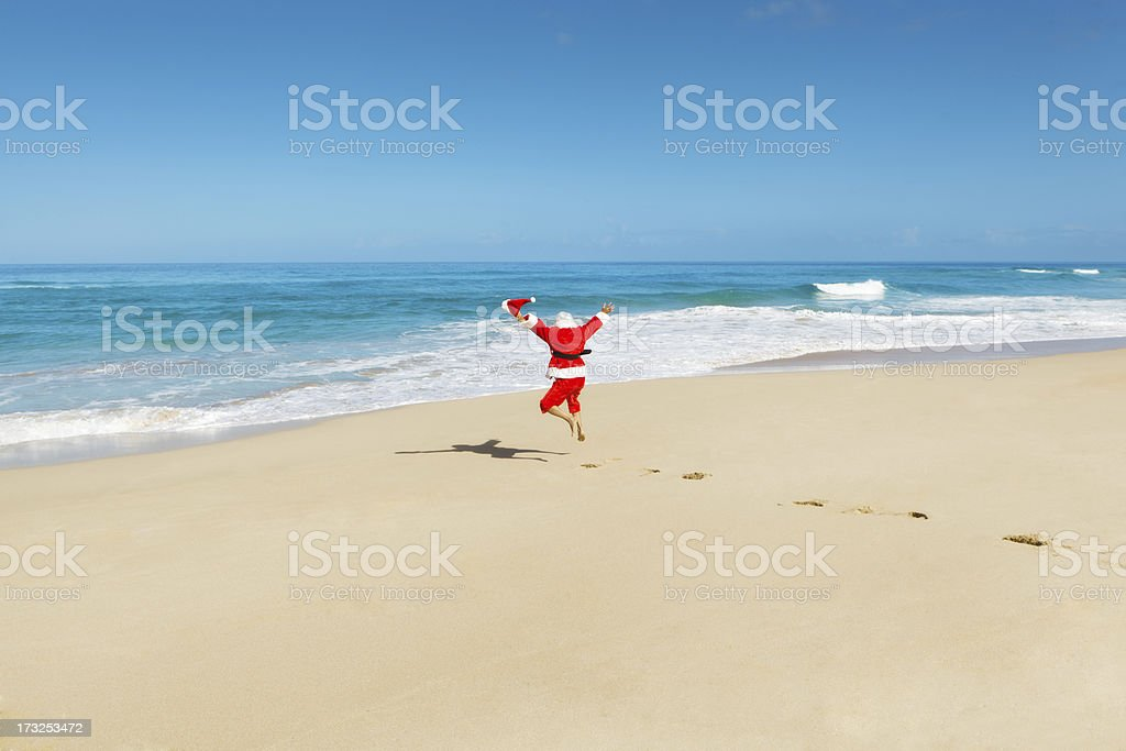 Happy Excited Jumping Santa Claus on Tropical Beach Vacation Hz stock photo