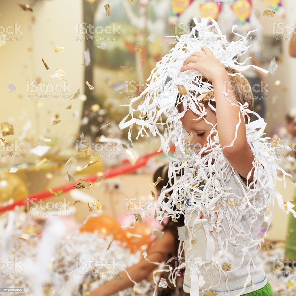 Happy excited laughing kid under sparkling confetti shower stock photo