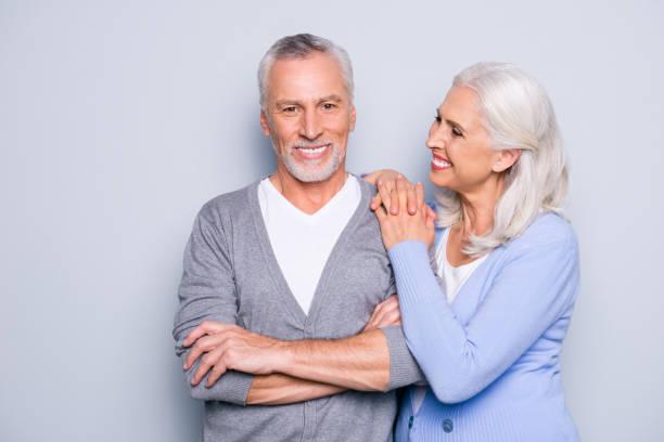 glückliche aufgeregte schöne zarte sanfte süße ältere menschen lächeln und umarmen, auf grauem hintergrund isoliert - zahnimplantat stock-fotos und bilder
