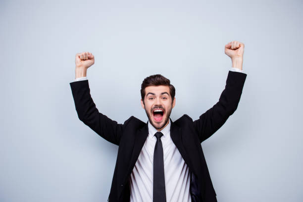 Happy excited man triumphing with raised fists on gray background Happy excited man triumphing with raised fists on gray background yeah right stock pictures, royalty-free photos & images