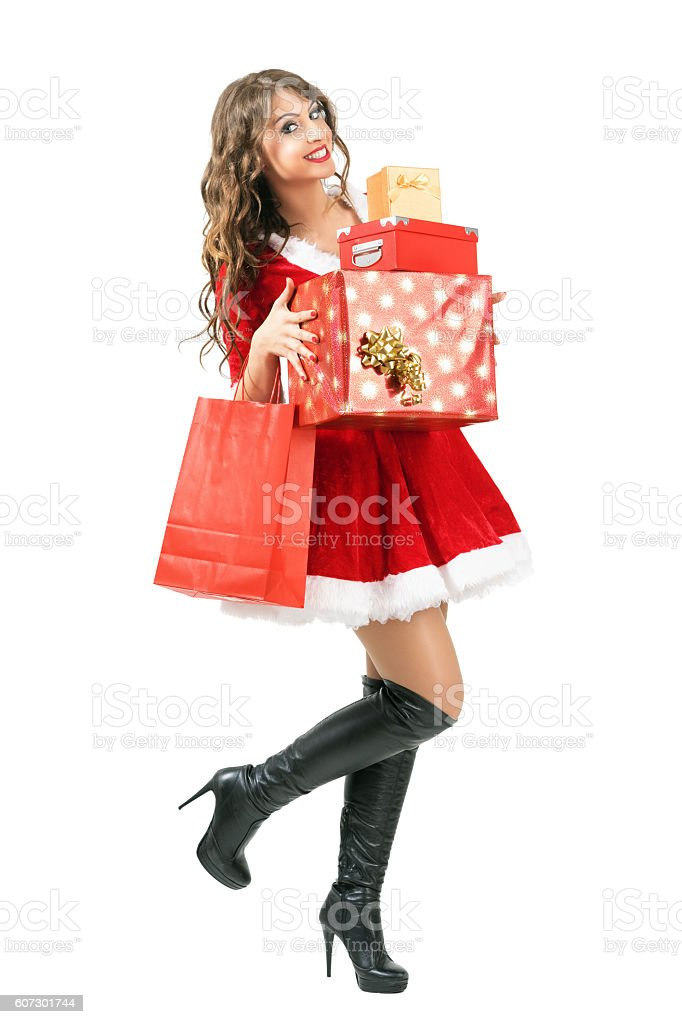 Happy excited Santa Claus woman carrying lots of gifts walking stock photo