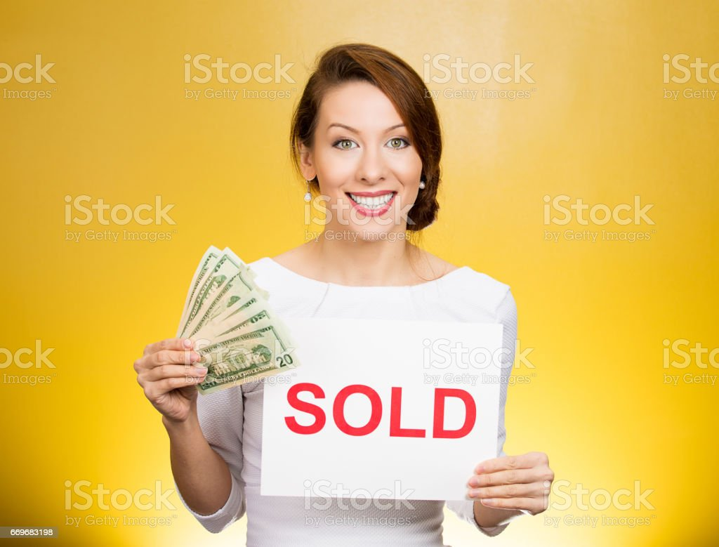 happy excited successful young business woman holding red sold sign and cash dollar bills stock photo