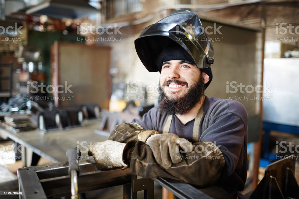 Happy excited welder enjoying manual work in factory shop stock photo