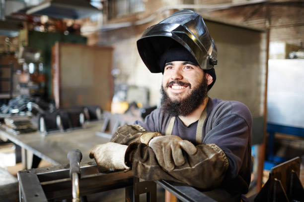 Happy excited welder enjoying manual work in factory shop Cheerful dreamy bearded young man with dirty sleeves wearing welding mask and looking with burning eyes while leaning on metal part in factory shop metal worker stock pictures, royalty-free photos & images