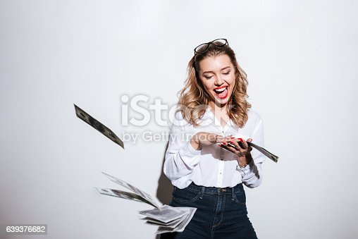 istock Happy excited woman throwing money 639376682