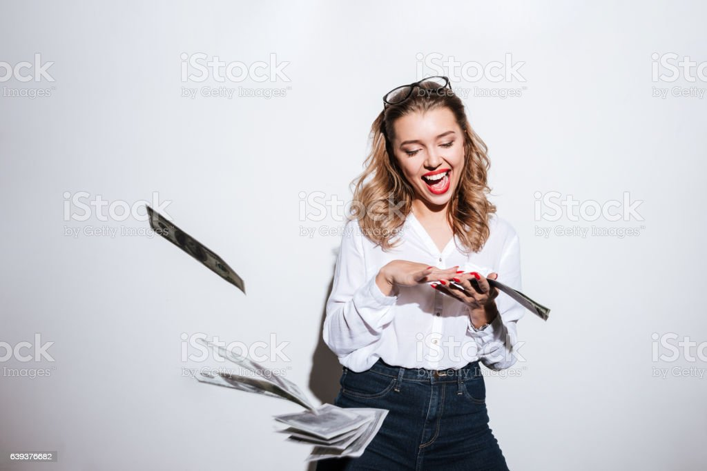 Happy excited woman throwing money stock photo