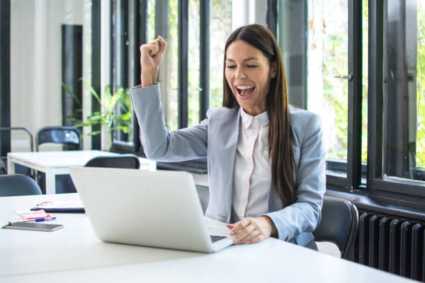Happy excited woman working on laptop and triumphing with fist up in office. Achievement and satisfaction concept. stock photo