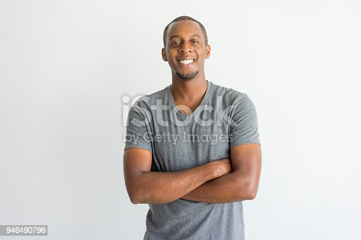 istock Happy excited young African man crossing arms on chest 946490796