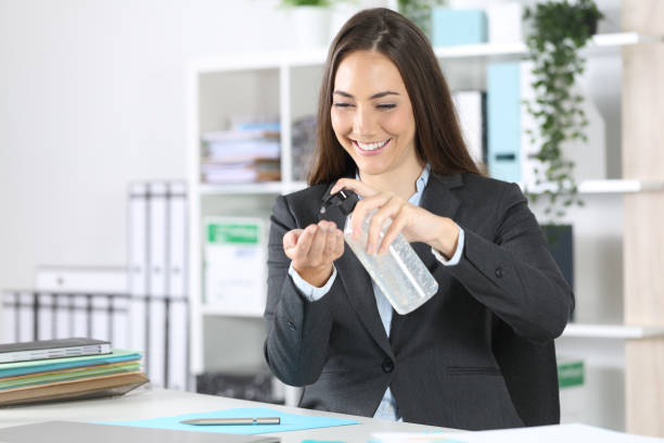 Happy executive applying hand sanitizer at office stock photo