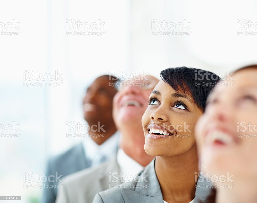 Happy executive with her colleagues looking up royalty-free stock photo
