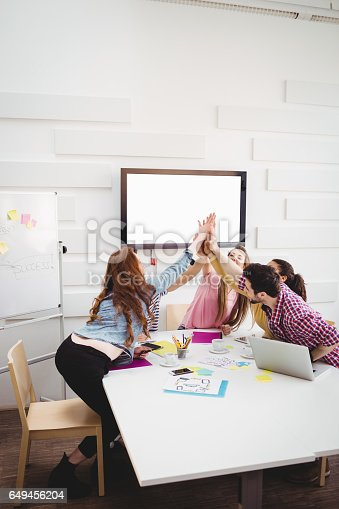 649403294 istock photo Happy executives giving high-five in meeting at creative office 649456204