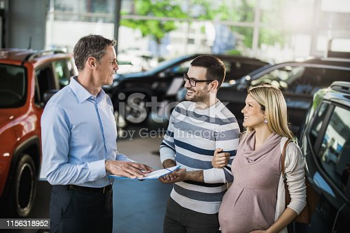 Happy pregnant couple talking to car salesperson in a showroom.