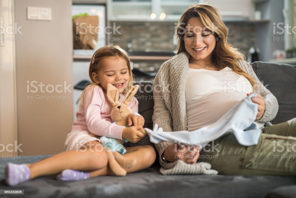 Happy expecting mother and her daughter looking new baby clothes at home. zbiór zdjęć royalty-free