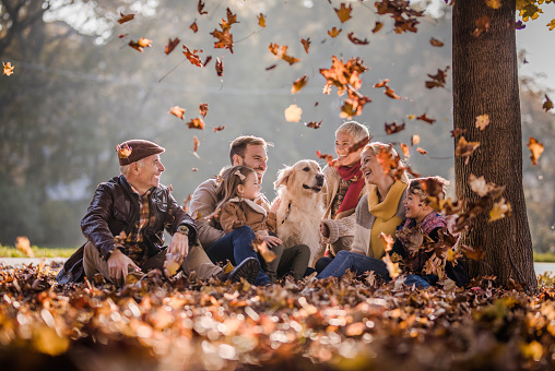 Happy multi-generation family and their dog relaxing in autumn leaves at the park.