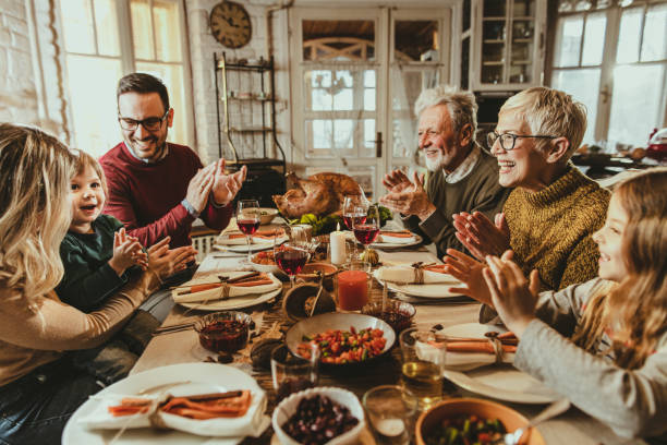 happy extended family applauding during thanksgiving meal at dining table. - thanksgiving стоковые фото и изображения