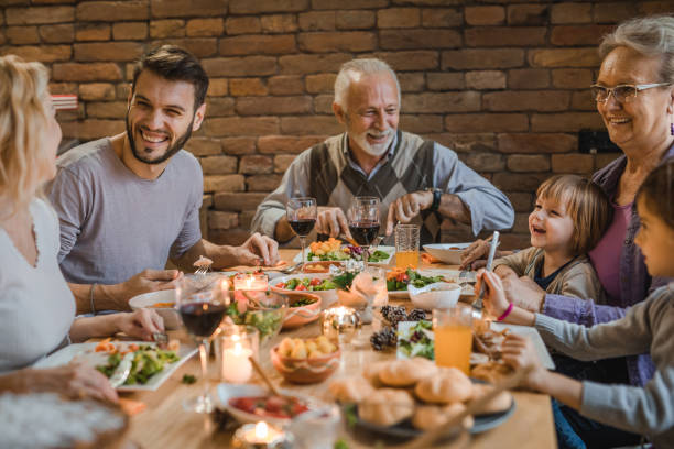 happy extended family communicating while having a dinner at dining table. - dining table stock photos and pictures