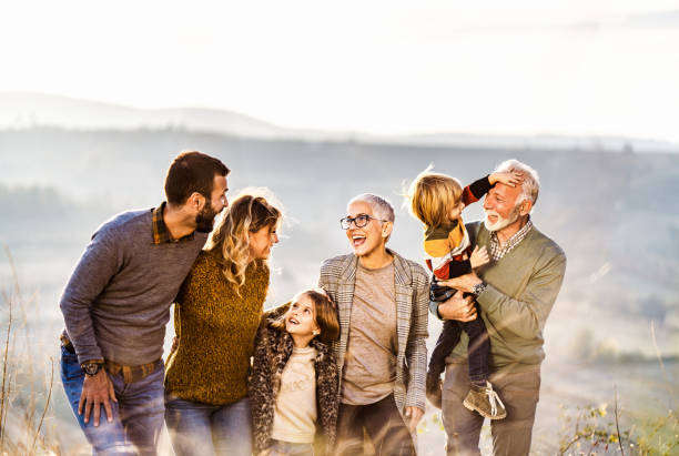 Happy extended family communicating while walking in autumn day on a hill. stock photo