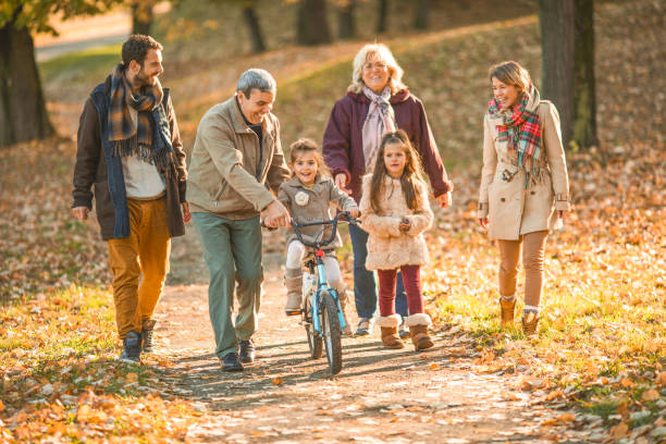 Happy extended family enjoying in autumn day at the park. stock photo