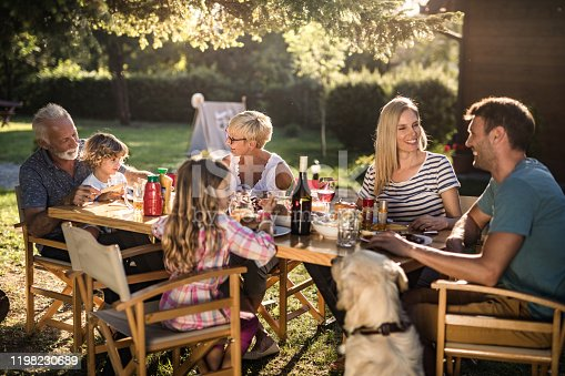 Happy multi-generation family enjoying in lunch time at their backyard.