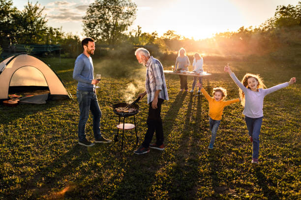 Happy extended family having a barbecue garden party at sunset. stock photo