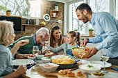 istock Happy extended family having fun during family lunch in dining room. 1215369487