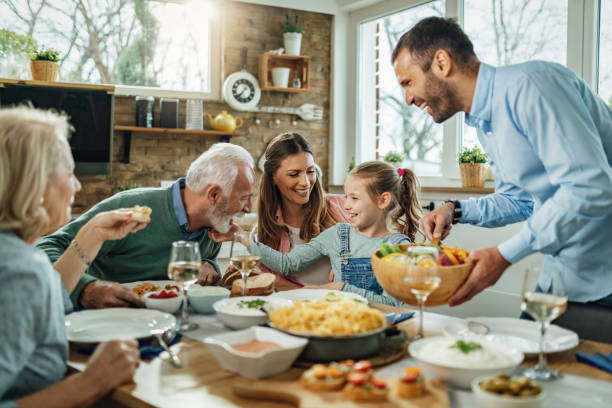 Happy extended family having fun during family lunch in dining room. stock photo