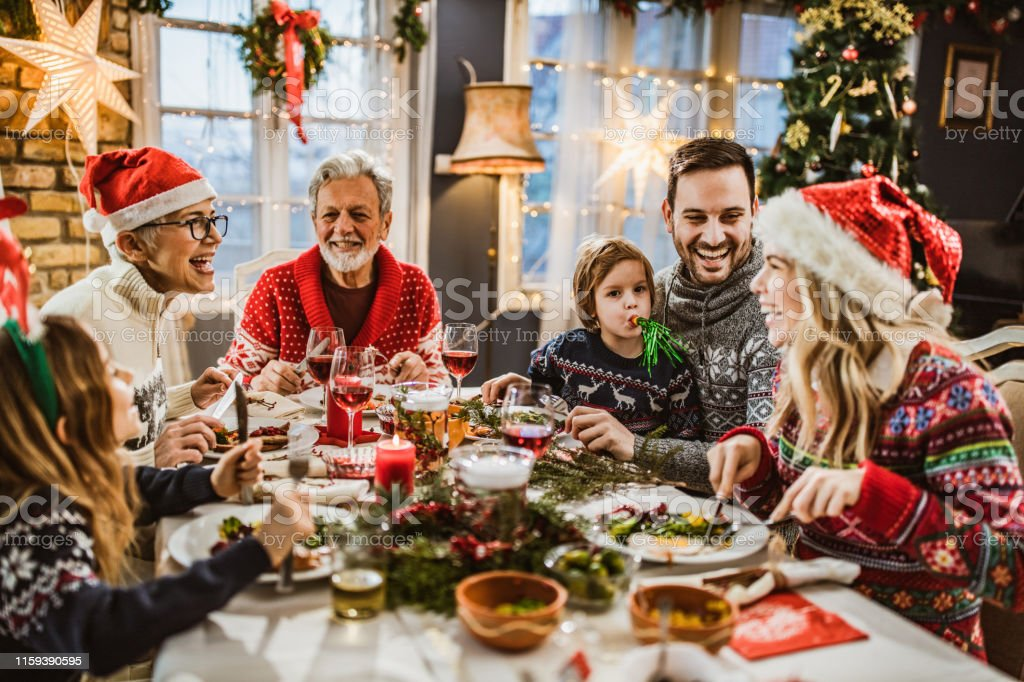 Happy extended family having New Year's lunch at dining table. - Foto stock royalty-free di Adulto
