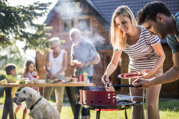 Happy extended family preparing barbecue in the backyard. Young happy parents preparing barbecue for their family's garden party. Focus is on woman. family bbq stock pictures, royalty-free photos & images