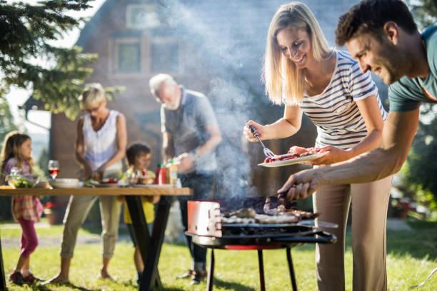 glückliche großfamilie vorbereitung grill im garten. - grillen garten stock-fotos und bilder