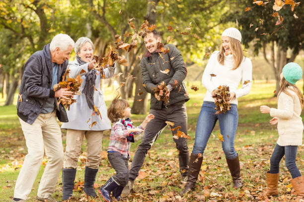 Happy extended family throwing leaves around stock photo