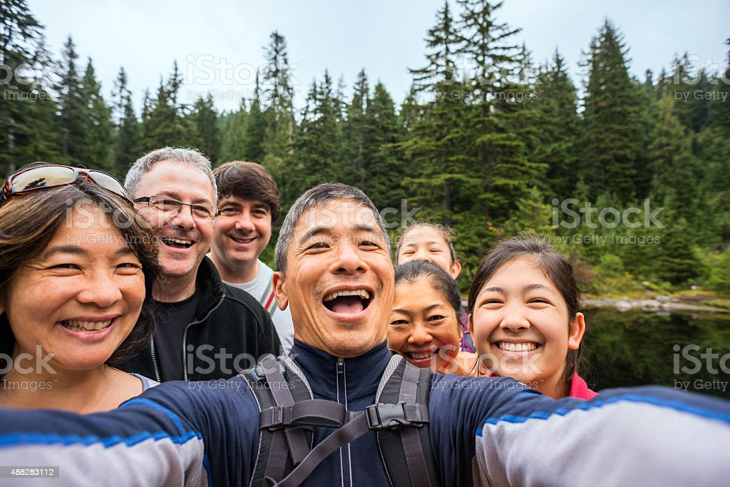 Happy, Extended Multi-Ethnic Family Taking Selfie While Hiking in Woods stock photo