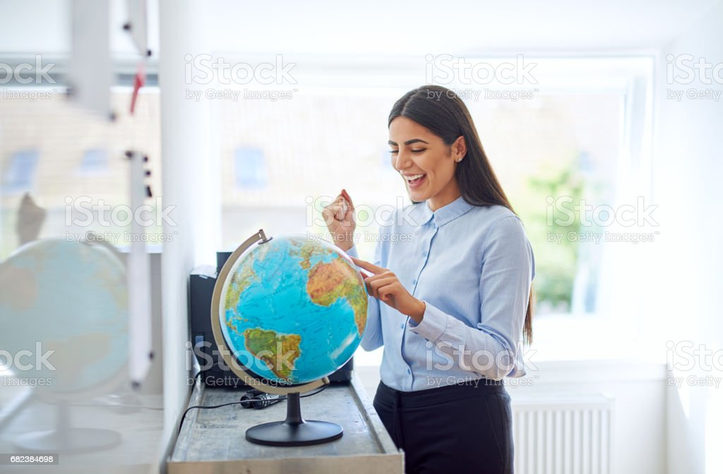 Happy exuberant young woman planning a trip stock photo