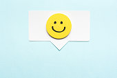 Happy face emoticon smiling comment on speech bubble and blue background. Social media marketing concept.