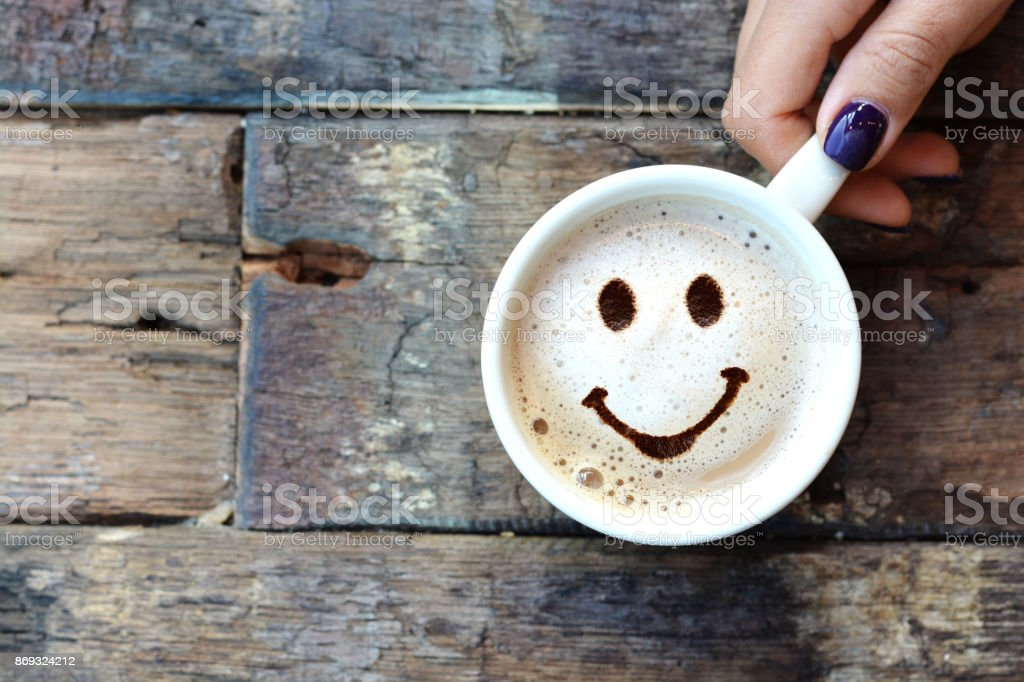 Happy face on cappuccino foam, woman hands holding one cappuccino cup on wooden table stock photo
