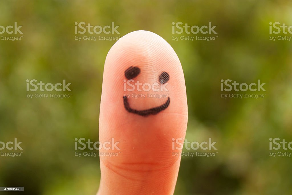 Happy face on finger stock photo
