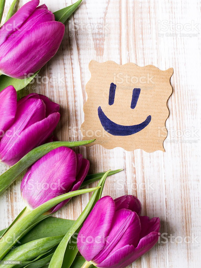 Happy face on paper and bouquet of tulip stock photo more pictures happy face on paper and bouquet of tulip royalty free stock photo izmirmasajfo