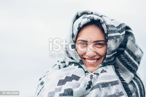 Smiling young woman wrapped in a blanket