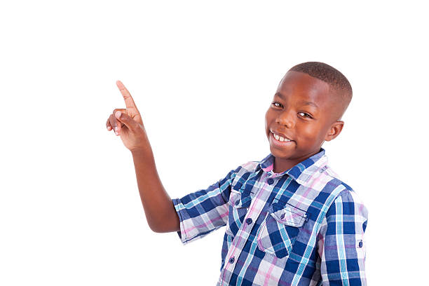 Happy faced boy in blue plaid shirt pointing at the ceiling stock photo