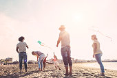 Happy familes flying with kite and having fun on the beach - Parents playing with children outdoor - Travel,love and holidays concept - Main focus on left couple